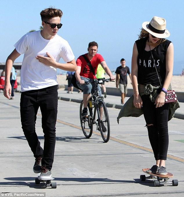 女一角而成名的17岁女星科洛-莫瑞兹约会.两人在沙滩上踩着滑板
