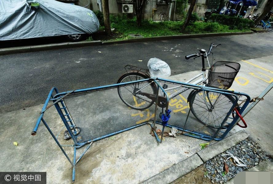 图为自行车与折叠床一起占车位.图片来源:视觉中国-小区居民为抢