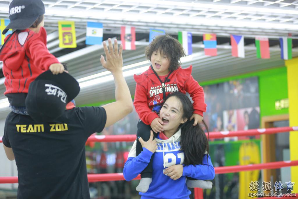 拳王邹市明一家四口在拳击台上打拳,邹市明的两个儿子轩轩和皓皓穿图片
