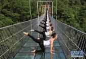 5月14日,瑜伽爱好者在广西一悬索玻璃桥上展示瑜伽。悬索玻璃桥由数百块全透明玻璃铺设而成。