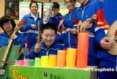 12月10日,北京五中分校的学生正在用废纸、饮料罐等废旧物品制作的乐器演奏乐曲,向众人宣传环保节能常...