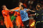 """乌拉圭和荷兰比赛结束之后,当荷兰队友开始庆祝胜利时,乌拉圭队球员们立即找到裁判进行理论,并形成了""""围..."""